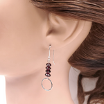 Silver earrings with 4 garnet stacked beads and a silver circle hanging below
