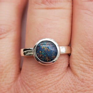 Opal triplet ring shown on someone's finger.