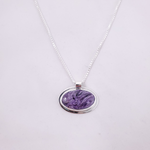 Oval charoite and sterling silver necklace hanging horizontally and with silver border around stone