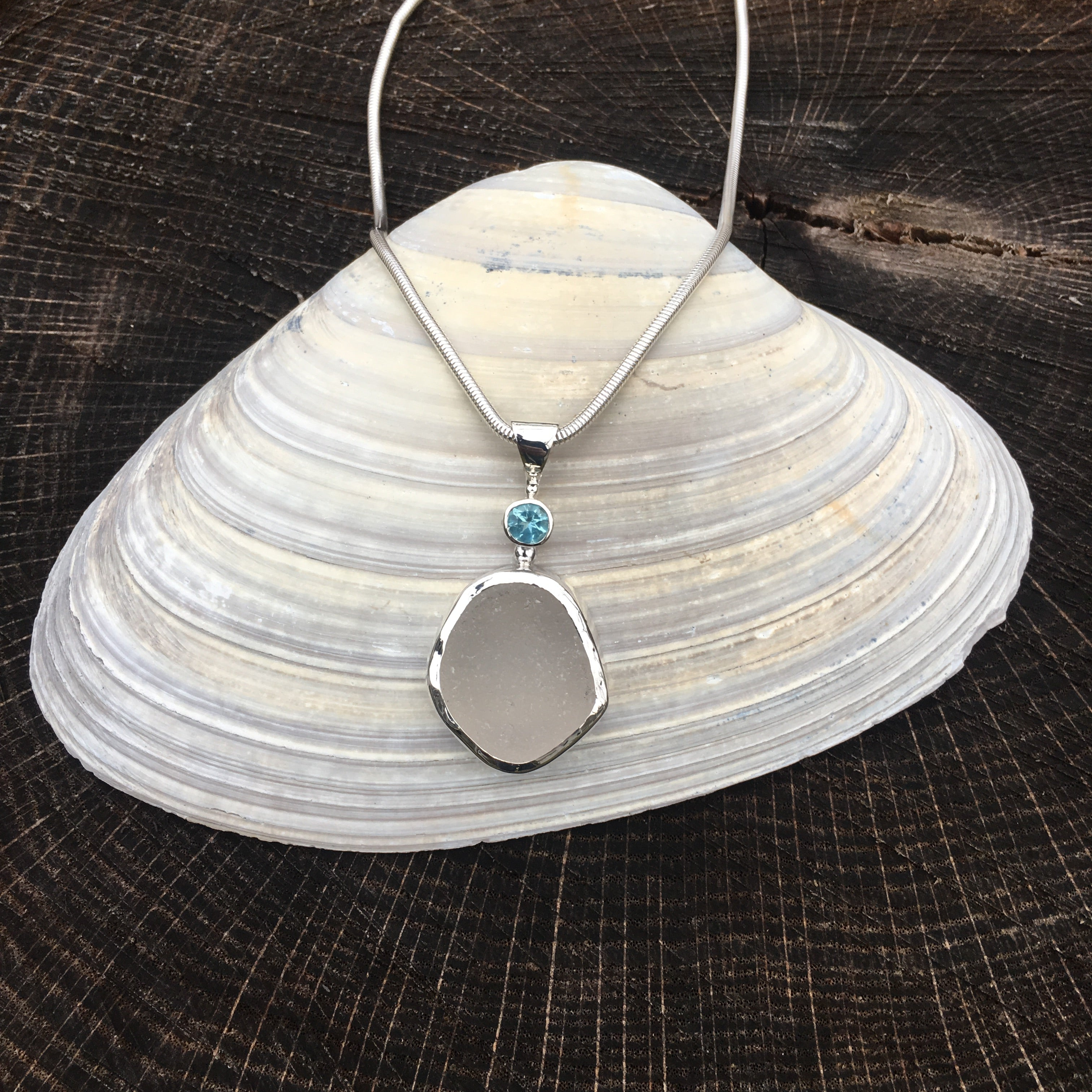 White sea glass and blue topaz bezel set necklace shown on shell.