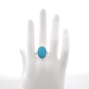 Oval bezel set turquoise ring shown on mannequin hand