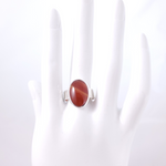 Reddish orange oval carnelian ring on mannequin hand