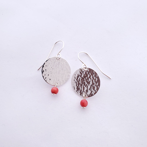 Hammered round silver disc earrings with small red coral beads hanging from bottom