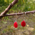 Red teardrop beaded dangle earrings displayed on tree branch