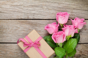 Photo of a wrapped box with 5 pink roses next to it