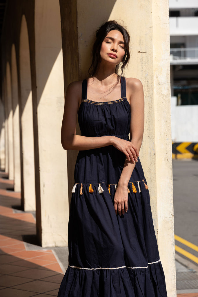 Woman dressed in a navy coloured, full length tiered cotton dress with yellow, orange and white hand-embroidered details and tassels leaning against a distressed pillar.