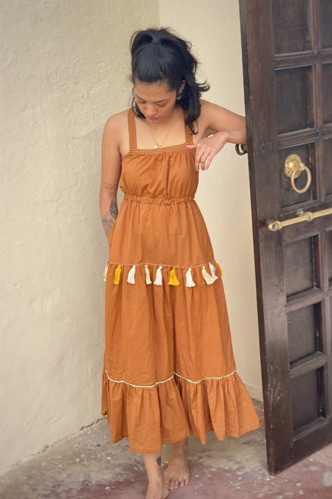 Woman dressed in a clay coloured, full length tiered cotton dress with yellow, orange and white hand embroidered details and tassels.