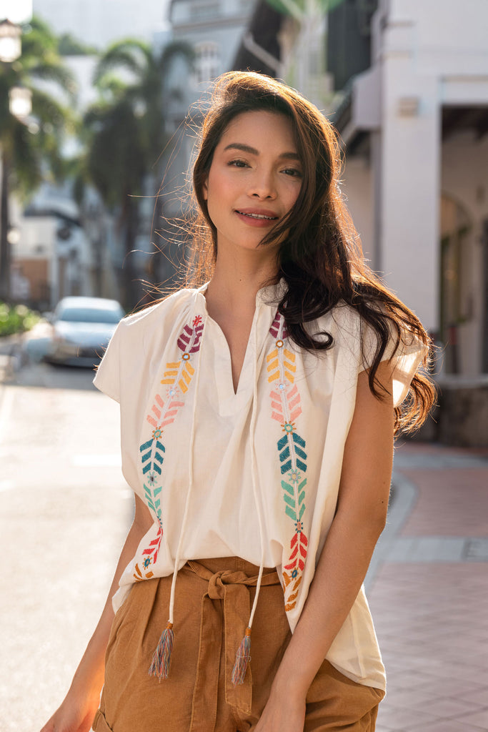 Woman in white cotton blouse with an open mandarin collar and intricate hand-stitched mirror embroidery detailing
