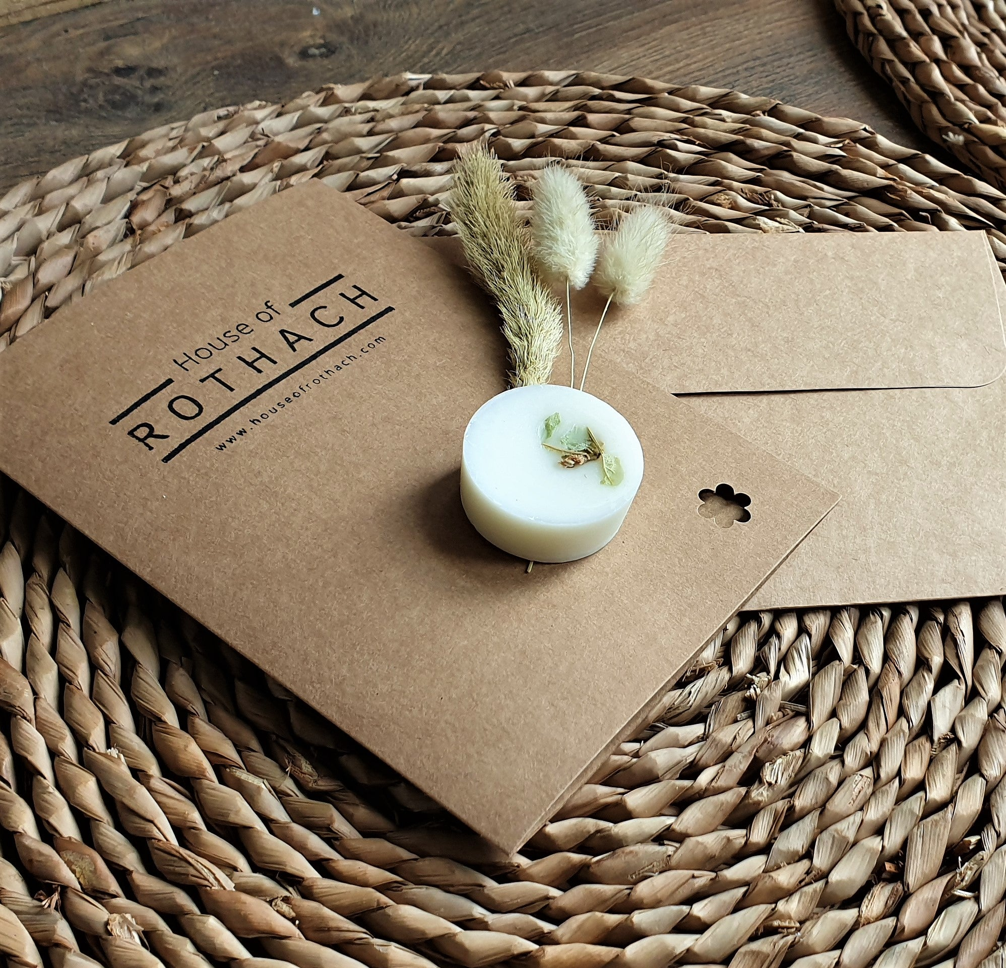 natural brown card with envelope sitting on a raffia mat on the floor. On top of the card is a single botanical wax melt with some dried flowers beside it. The card says  House of Rothach on it.