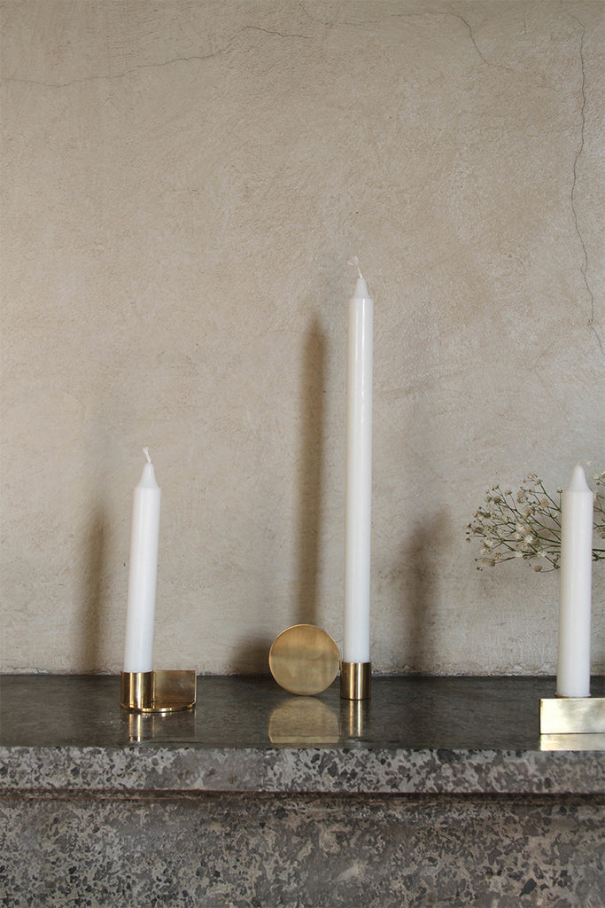Frama brass Fundamental Candleholders with tall white candles on a grey polished granite ledge - Mette Collections Australia (4517552848995)