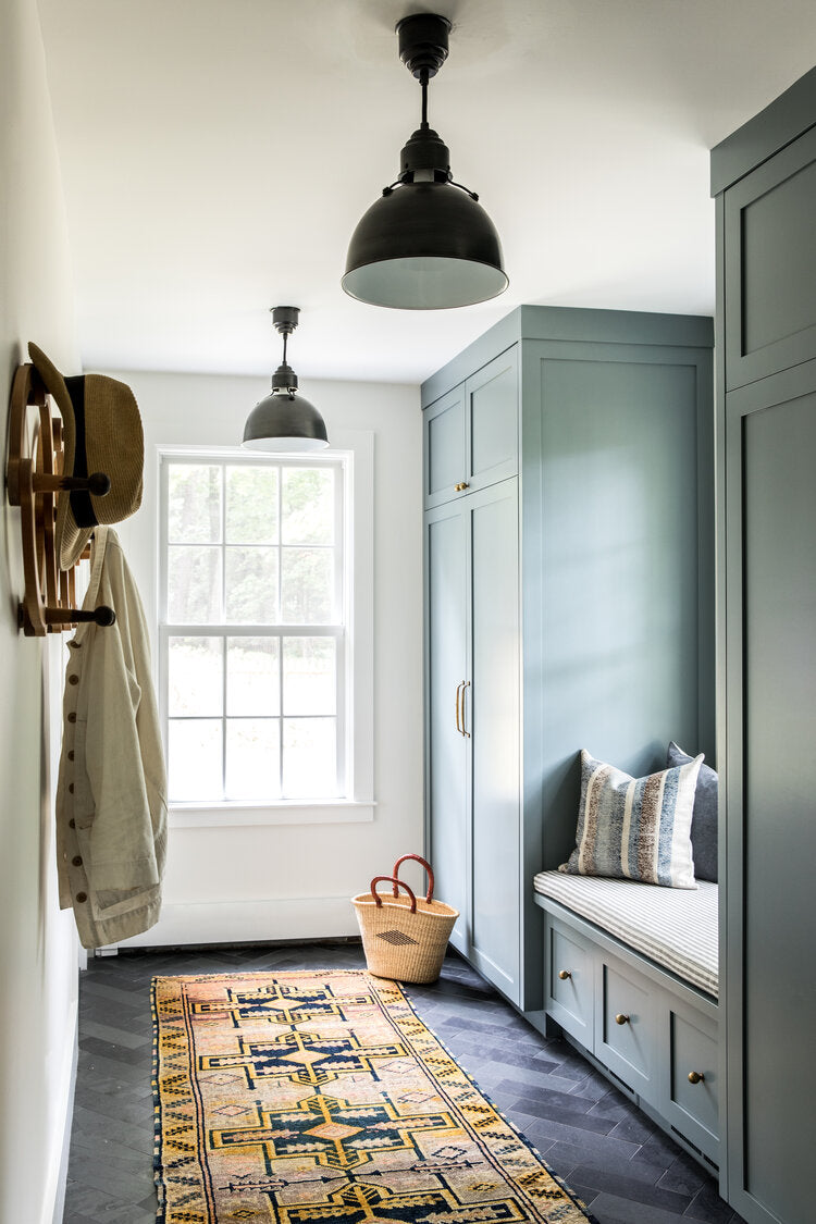 mudroom with green cabinets and slate floor
