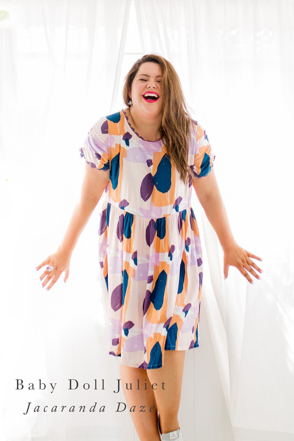 Baby Doll Juliet, a drop waist knee length dress with a cap sleeve in a colourful print of purple, blush and teal paint. Curvy model laughing in front of window.