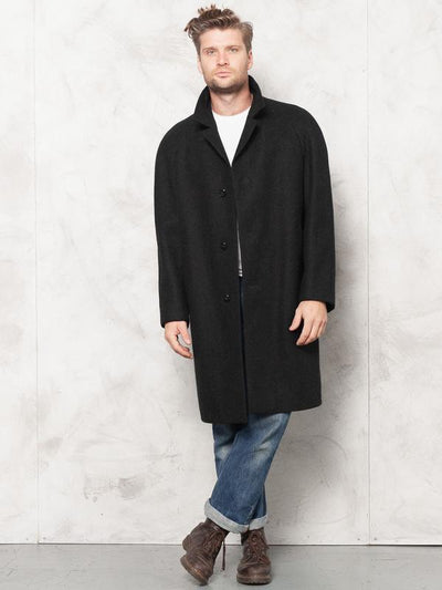 Model wearing minimalist 70's classic black wool coat in black color