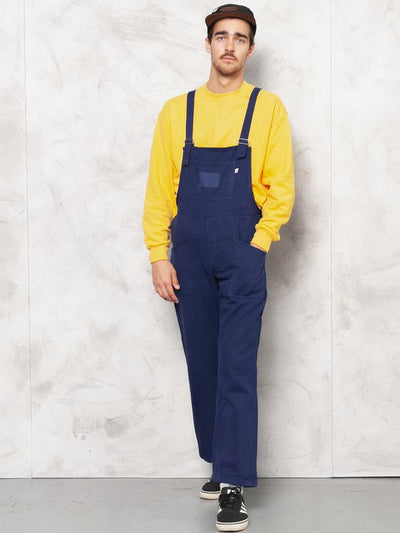 Model is wearing vintage 90s bib overall dungarees in navy blue color for men