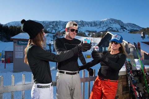 3 people celebrating after a day of skiing at Bridger Bowl. Drinking beer on the deck and while wearing Jelt Belts on their ski pants.
