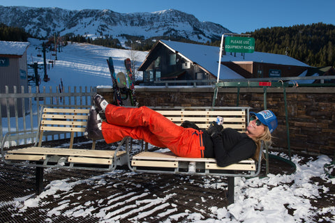 Jen Perry laying on bench enjoying a beer after a day skiing at Bridger Bowl. Wearing orange ski pants with a river turquoise Jelt Belt