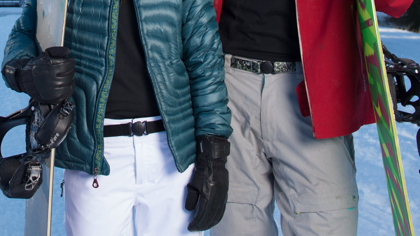 Man and woman wearing ski gear with Jelt elastic stretch belts in black granite and digital camo.
