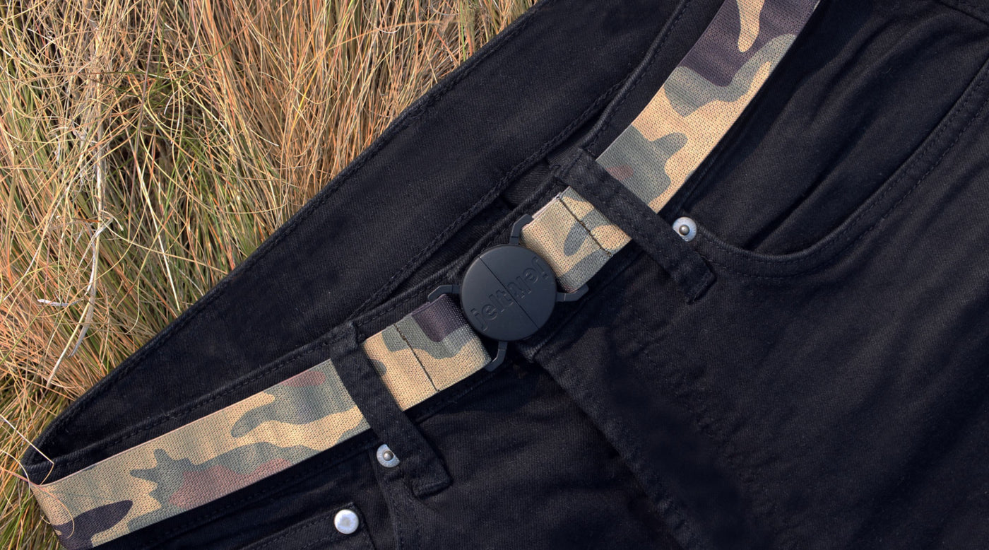 Jelt True Camo elastic belt pictured on a pair of black jeans and laying in grassy area
