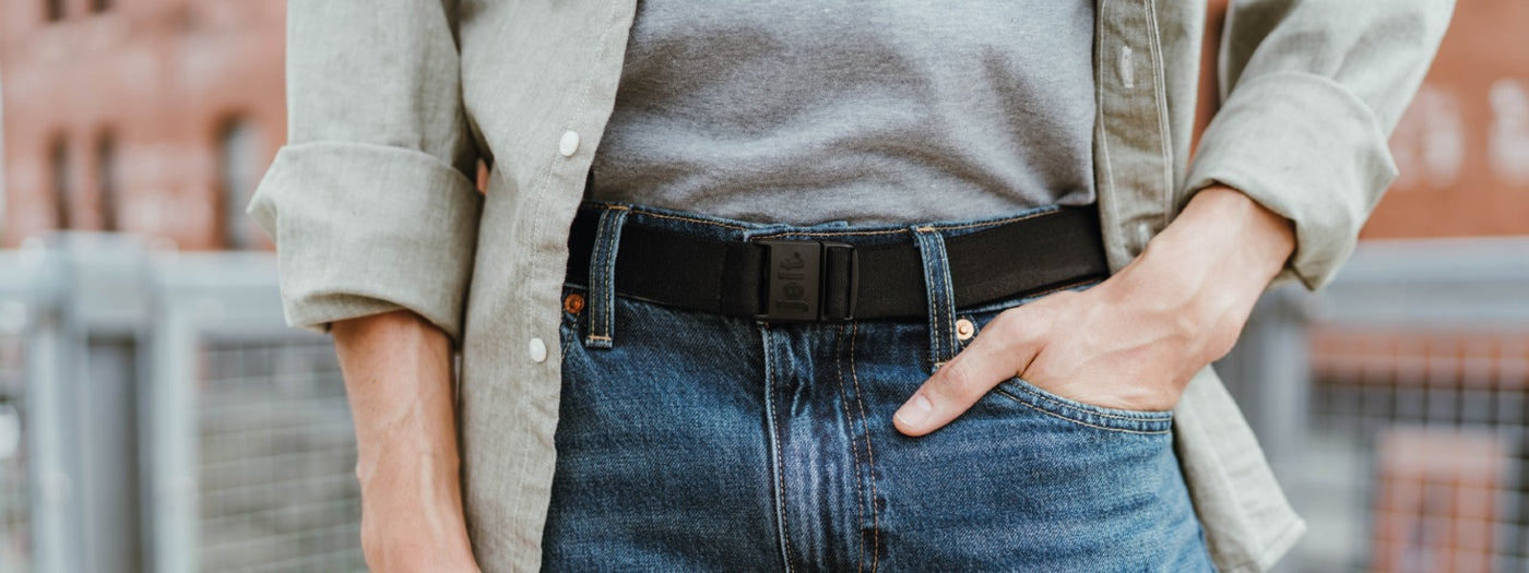 Man pictured wearing JeltX Adjustable elastic belt in black with jeans, t-shirt and button down shirt.