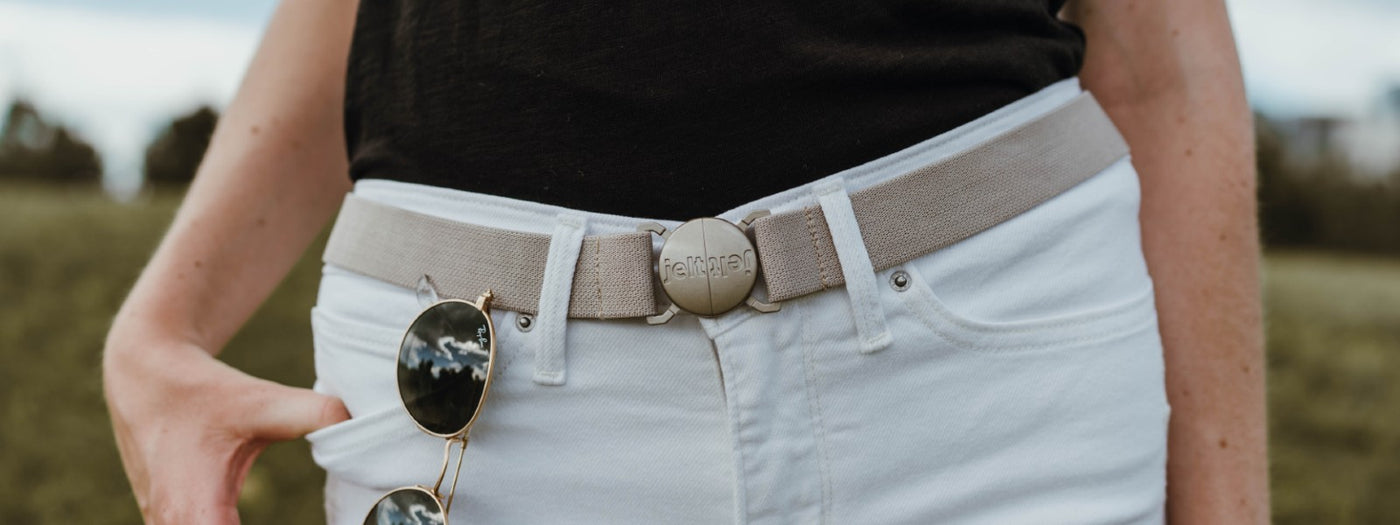 Woman wearing a Khaki Tan Jelt elastic belt with a black shirt and white pants with sunglasses hanging on her pocket.