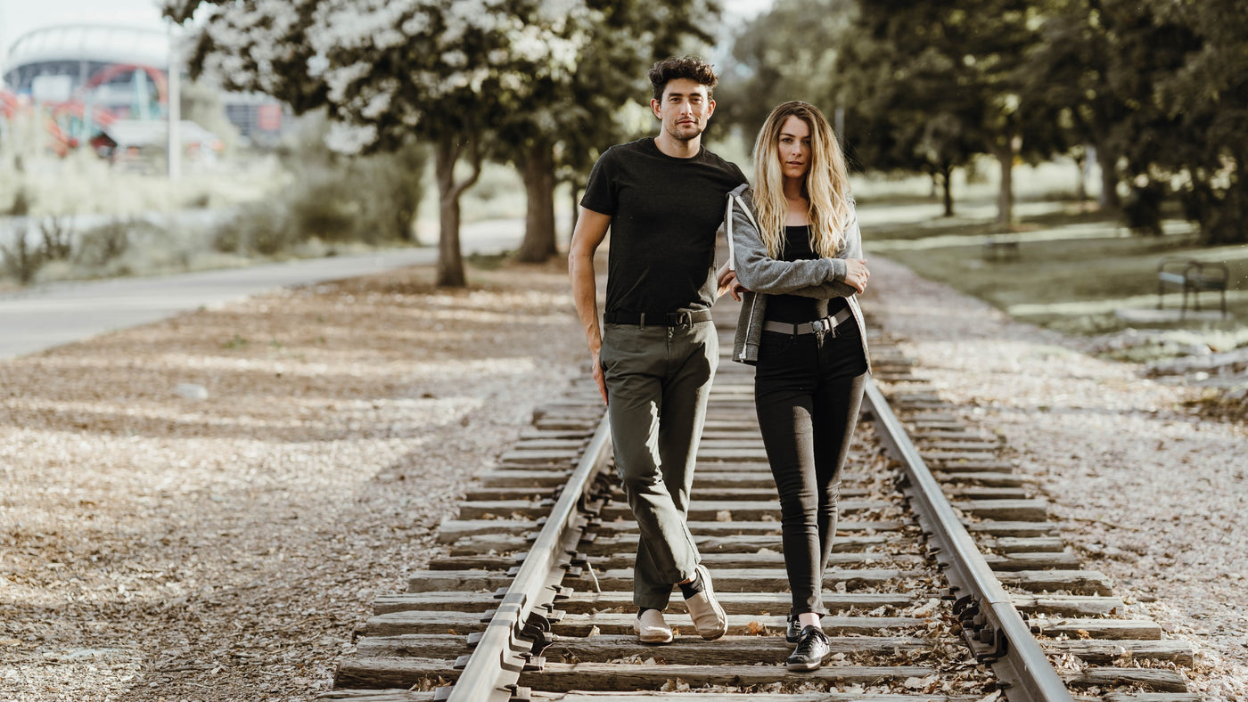 Couple on train tracks. Man wearing JeltX with khaki pants and a woman wearing a steel grey original belt with black shirt and pants