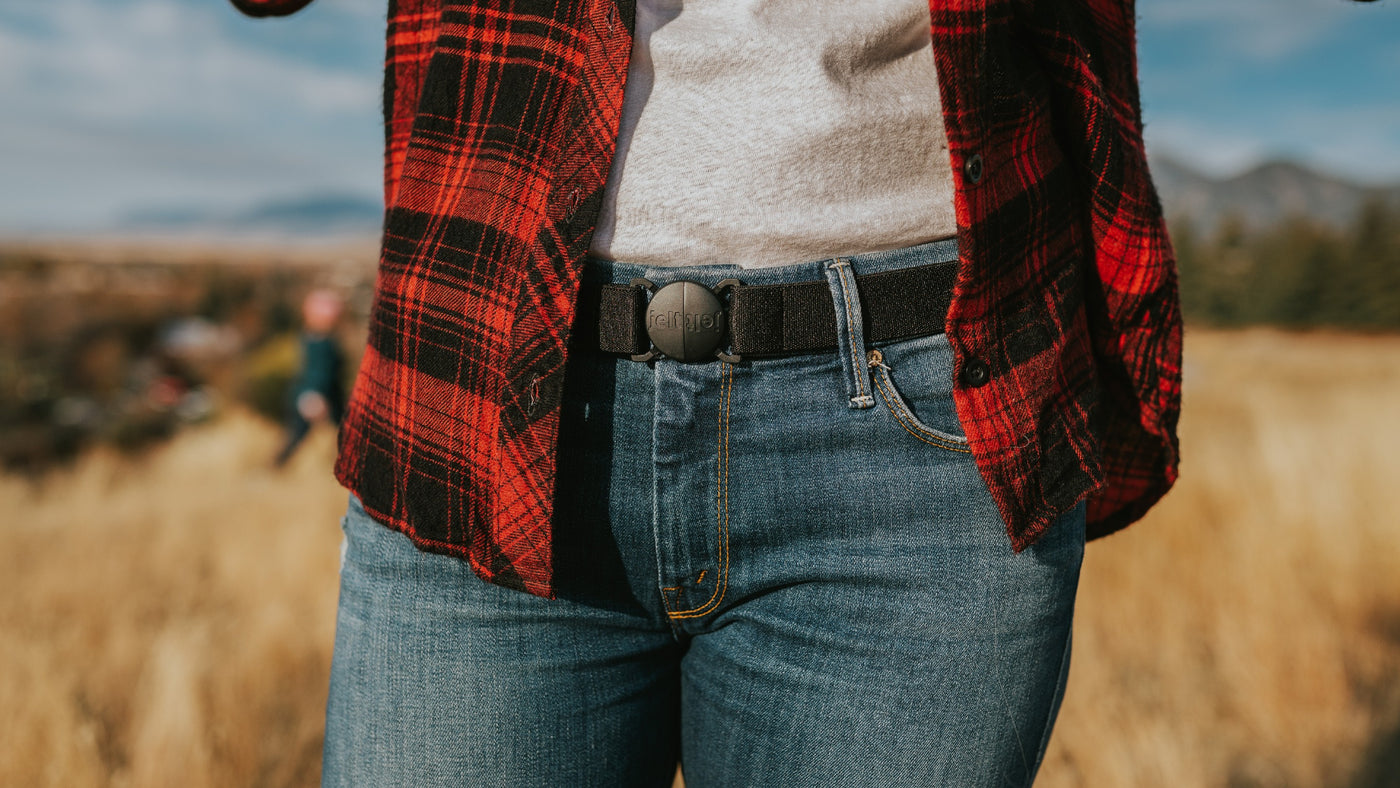 Woman wearing Jelt original elastic stretch belt in Black Granite. She is wearing the Jelt belt on jeans, with a white shirt and red and black flannel shirt.
