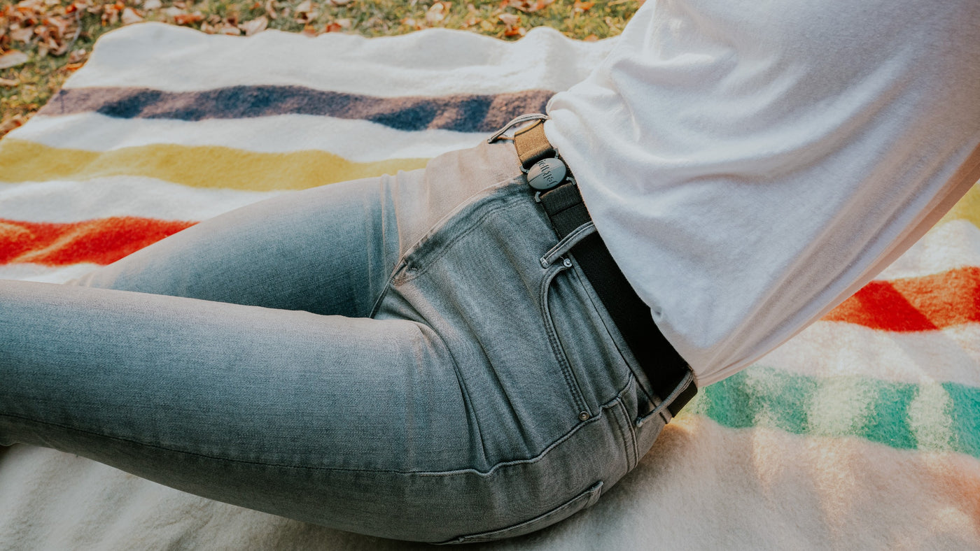 Woman wearing a Jelt in Granite Black with a white t-shirt and grey jeans, while laying on a blanket in a park.