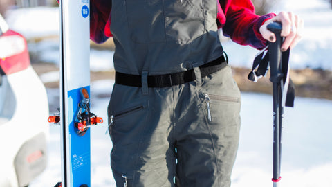 Woman wearing JeltX Adjustable elastic stretch belt in black with ski bibs. Holding skis and ski poles.