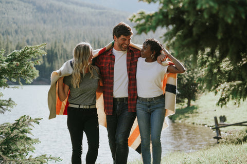 A group of friends all wearing Jelt belts and wrapped in a Pendleton blanket walking in front of a mountain lake