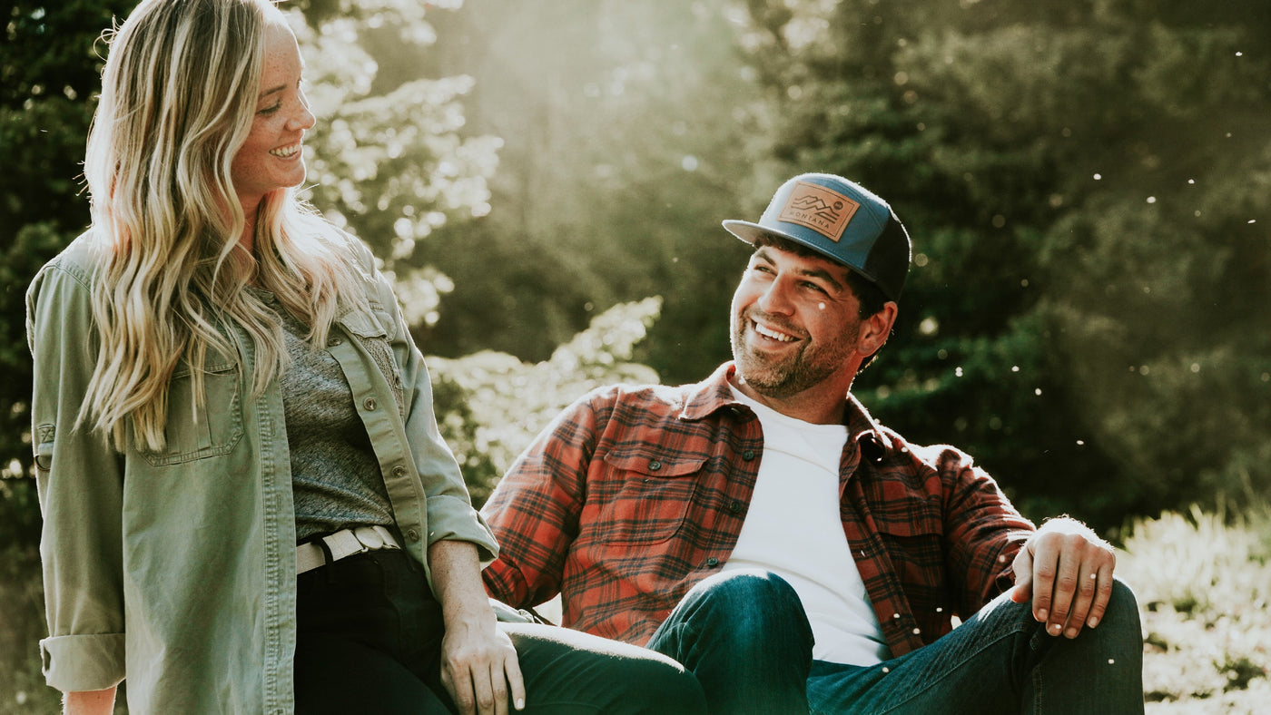 Couple sitting at campfire. The woman wearing a Jelt original elastic belt in Khaki Tan with a khaki green jacket and black pants. The man is wearing a Jelt 7-panel hat in navy with a flannel, jeans and a Jelt Venture Adjustable belt.