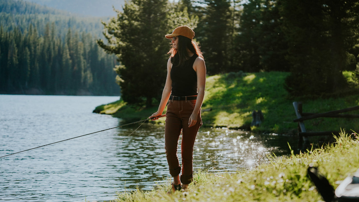 Woman wearing JeltX Adjustable elastic bel on brown pants and black tank while fishing on lake. Also wearing Jelt branded corduroy cap in mustard yellow.