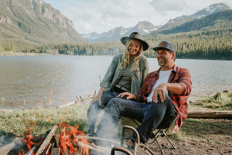 Man and woman sitting around a fire in front of mountain lake. The couple are both wearing Jelt elastic stretch belts with their mountain chic attire.