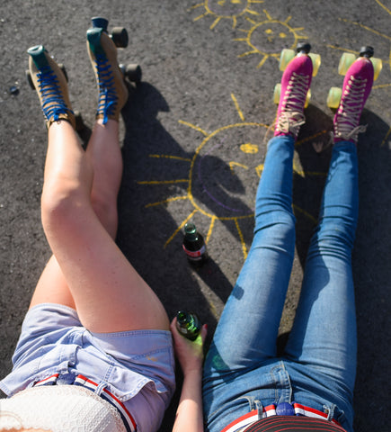 Girls wearing roller skates, sitting on pavement. Wearing Jelt USA Stripe Elastic stretch belts with their summertime look.