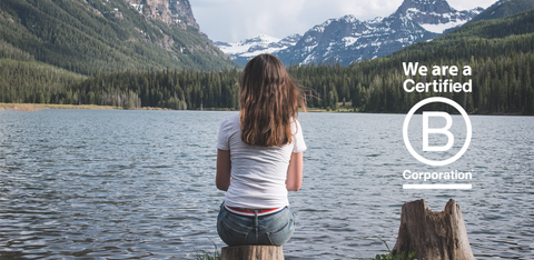 "Jelt image of girl wearing USA belt while sitting on a stump looking onto a Hyalite Lake, with a ""We are Certified B Corporation"" for Jelt"