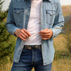 Man wearing Jelt True Camo elastic belt with a white t-shirt, denim button down shirt and jeans.