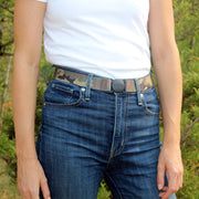 Woman wearing a Jelt True Camo elastic belt with a white t-shirt and jeans