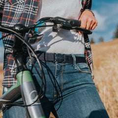 Woman wearing a Denim Navy Jelt elastic belt with jeans and flannel, while walking bike
