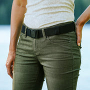 Woman wearing Jelt Venture adjustable belt with green pants and a tank top.