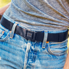 "Montana State University ""M"" JeltX Adjustable belt in navy by Jelt belts. Shown on a woman in jeans and grey shirt."