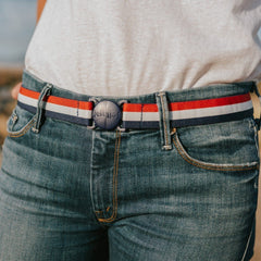Woman wearing USA red white and blue stripe Jelt elastic belt with jeans and white t-shirt