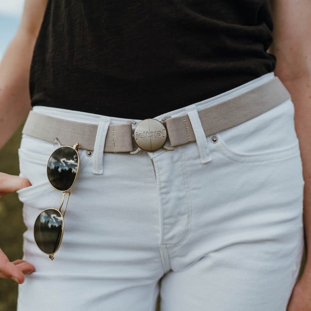 Khaki tan belt featured on a woman wearing white jeans