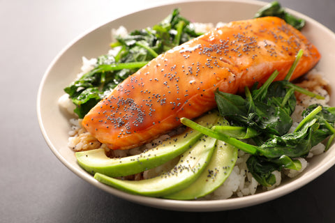 salmon with spinach and avocado on a plate