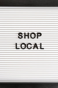 This is a simple call to shop local, the sign give this simple message in black letters on a slat-wall background