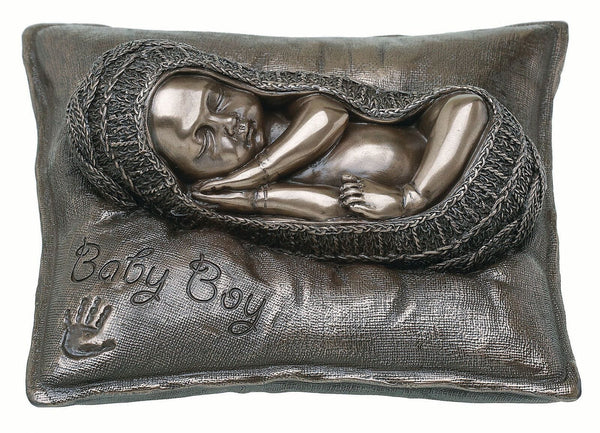 "This Genesis item shows a baby boy sleeping in a blanket on a soft cushion with ""baby boy"" and a baby hand print on it."