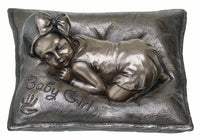 "This Genesis item shows a baby girl sleeping on a soft cushion with ""baby girl"" and a baby hand print on it."