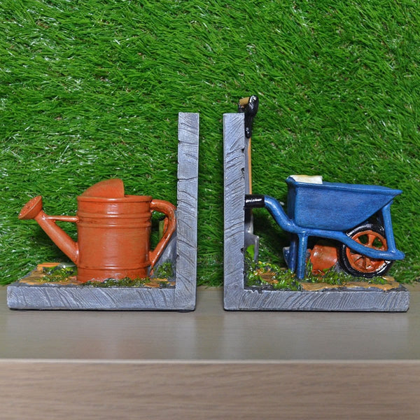 Gardening bookends has a watering can on one side and a wheelbarrow, shovel and white gloves on the other side