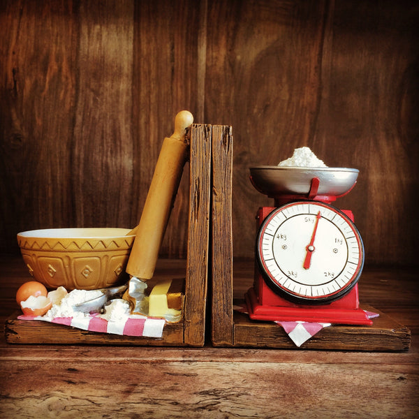 Bakery bookend are two bookends that have a measure scales with flour on it also the other side has a bowl, a rolling pin and some egg shells