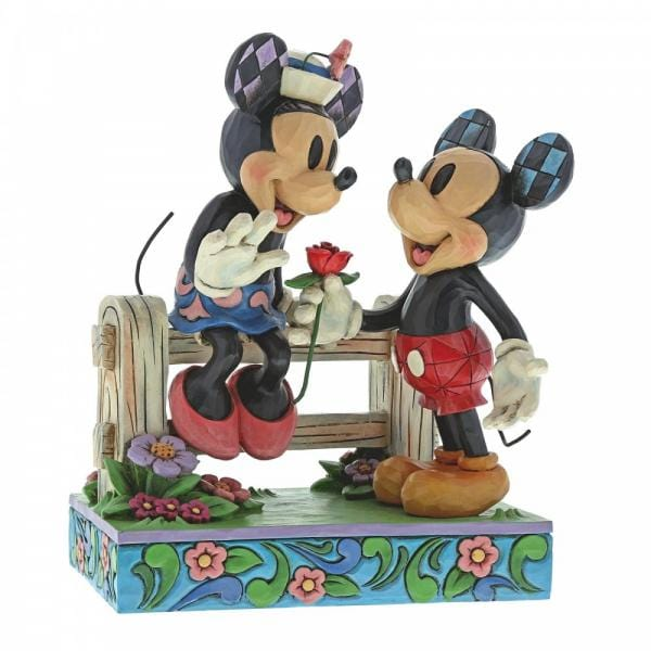 Disney characters Millie Mouse sitting on a fence being offered a red rose by her paramour Mickey Mouse.  Standing on a border of flowers