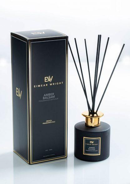 This picture shows a glass diffuser with a gold collar and designed in Ireland, with its packaging (elegant black packaging with gold ink), French fragrance oils scented Amber Balsam from Eimear Wright. Lovely fragrance best seller.