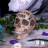Tattoo fund money box is a skull with tattoos over the head and face with a slot for the coins